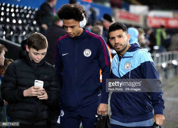 Manchester City's Leroy Sane and Sergio Aguero take selfies with young fans as they arrive at the stadium prior to the Premier League match at the...