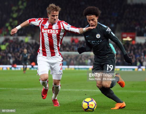 Manchester City's Leroy Sane and Stoke City's Moritz Bauer battle for the ball during the Premier League match at the bet365 Stadium Stoke