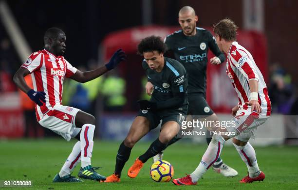 Manchester City's Leroy Sane battles for the ball with Stoke City's Moritz Bauer and Badou Ndiaye during the Premier League match at the bet365...