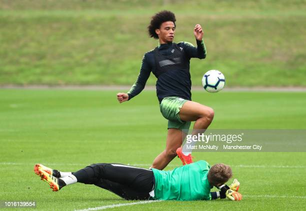 Manchester City's Leroy Sane takes on goalkeeper Daniel Grimshaw during training at Manchester City Football Academy on August 13 2018 in Manchester...