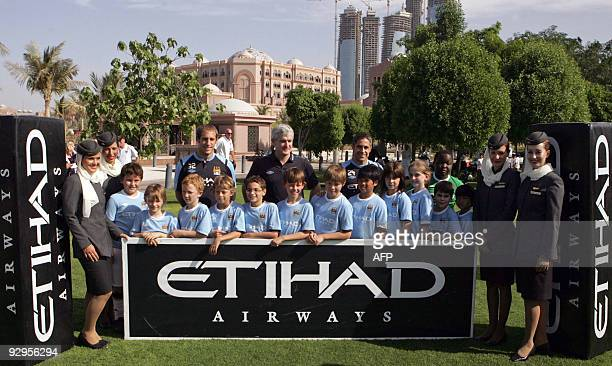 Manchester City's manager Mark Hughes Brazilian defender Sylvinho and Argentinian defender Pablo Zabaleta pose for a picture with children and Etihad...