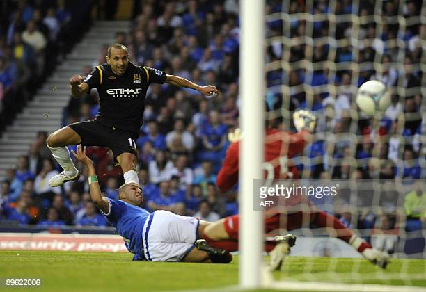 Manchester City's Martin Petrov scores his side's second goal as Rangers' Madjid Bougherra attempts tackle during their friendly soccer match at...