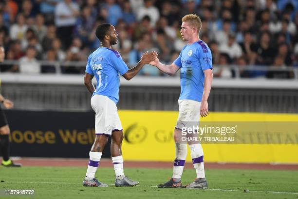 Manchester City's midfielder Raheem Sterling celebrates with teammate midfielder Kevin De Bruyne after scoring during a friendly football match...