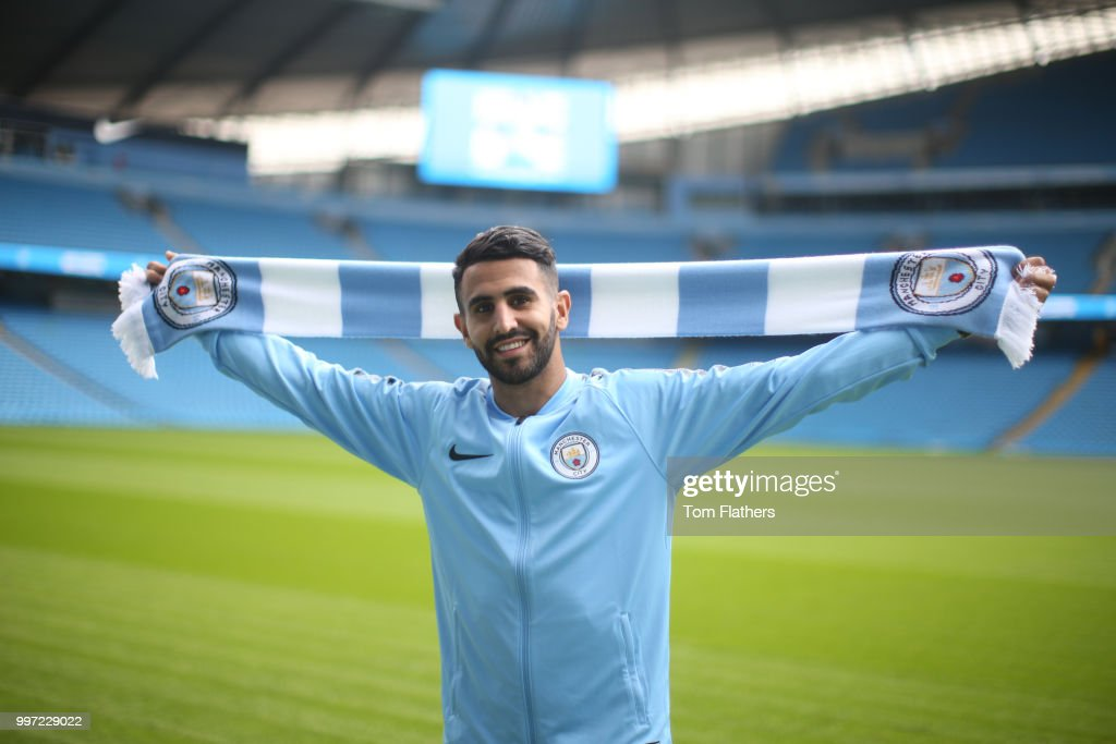 Manchester City's new signing Riyad Mahrez holds a scarf at the Etihad Stadium on July 12, 2018 in Manchester, England.