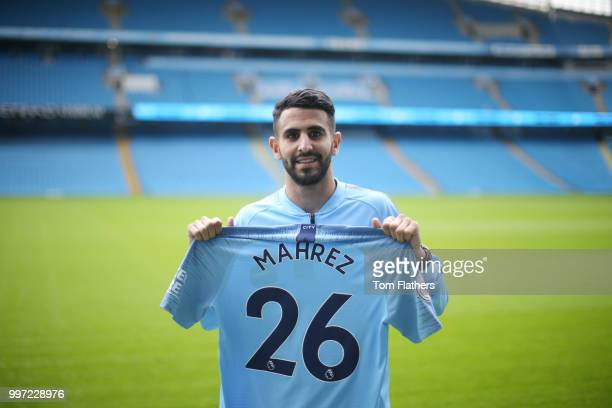 Manchester City's new signing Riyad Mahrez holds a shirt at the Etihad Stadium on July 12 2018 in Manchester England