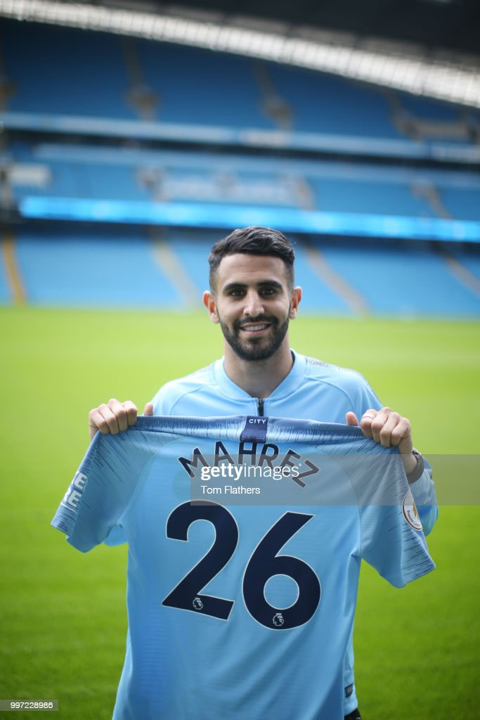 Manchester City's new signing Riyad Mahrez holds a shirt at the Etihad Stadium on July 12, 2018 in Manchester, England.