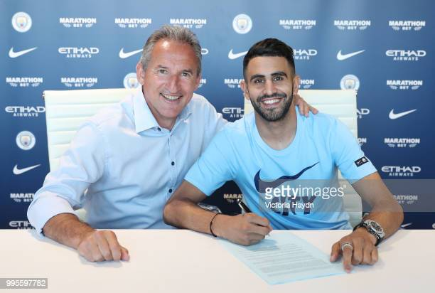 Manchester City's newest signing Riyad Mahrez has his photo taken with Txiki Begiristain at Manchester City Football Academy on July 10 2018 in...