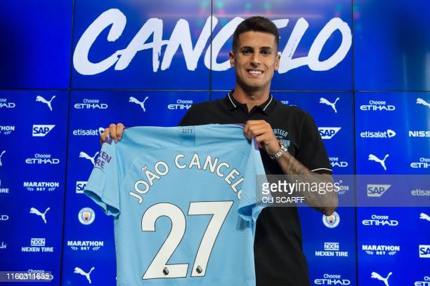Manchester City's newly signed Portuguese defender Joao Cancelo poses with his club shirt during his unveiling at the City Football Academy in...