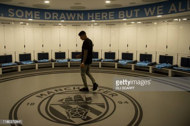 Manchester City's newly signed Portuguese defender Joao Cancelo poses for photographs in the Manchester City dressing room of the Etihad Stadium in...