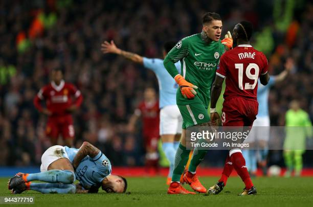 Manchester City's Nicolas Otamendi goes down from a challenge as Manchester City goalkeeper Ederson confronts Liverpool's Sadio Mane during the UEFA...