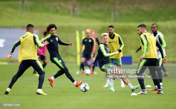 Manchester City's Oleksandr Zinchenko and teammates warm up during training at Manchester City Football Academy on August 29 2018 in Manchester...