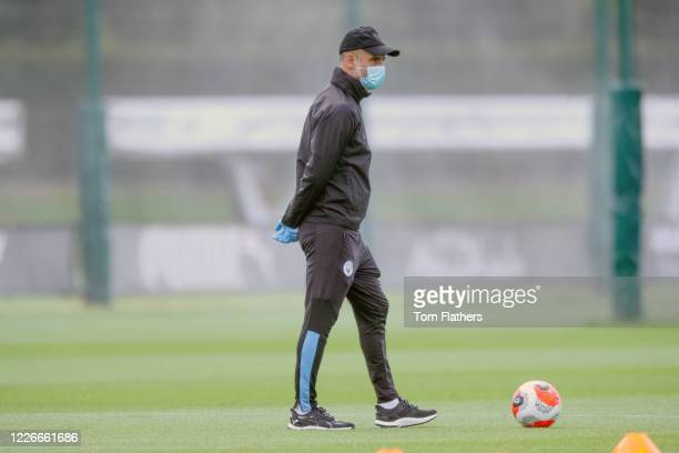 Manchester City's Pep Guardiola wearing a face mask watches his players during training at Manchester City Football Academy on May 23 2020 in...