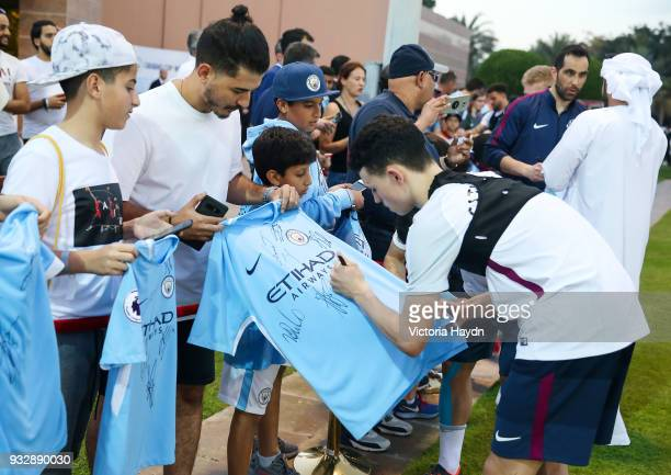 Manchester City's Phil Foden and Claudio Bravo sign shirts for fans during the training session on March 16 2018 in Abu Dhabi United Arab Emirates