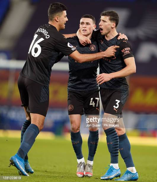 Manchester City's Phil Foden celebrates scoring the opening goal with Rodri and Ruben Dias during the Premier League match at Goodison Park,...