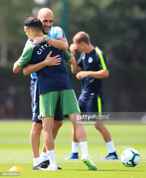 Manchester City's Phil Foden greets manager Pep Guardiola during training at Manchester City Football Academy on July 6 2018 in Manchester England