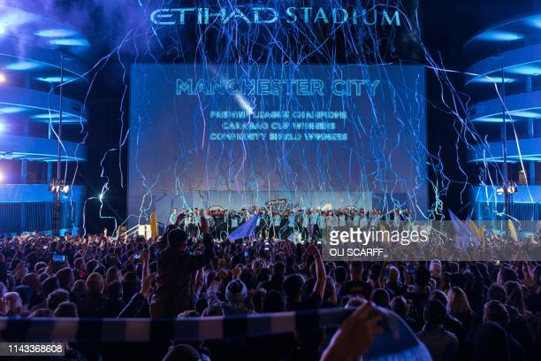 Manchester City's players and coaching staff present the Premier League trophy to supporters outside the Etihad Stadium in Manchester northern...