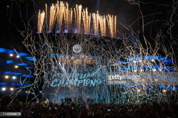 TOPSHOT Manchester City's players and coaching staff present the Premier League trophy to supporters outside the Etihad Stadium in Manchester...