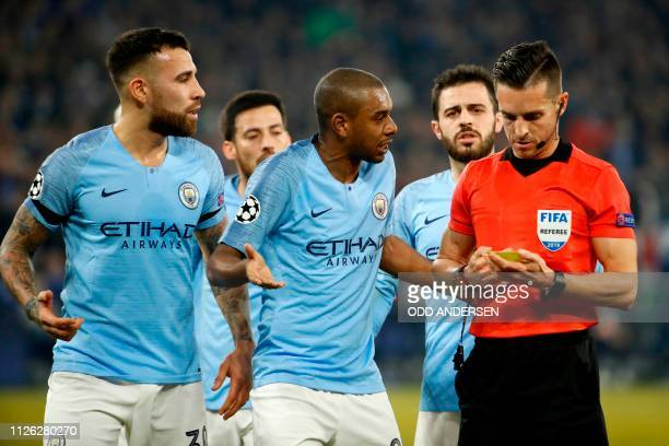 Manchester City's players argue with the referee after he gave the first penalty to Schalke following VAR deliberation during the UEFA Champions...