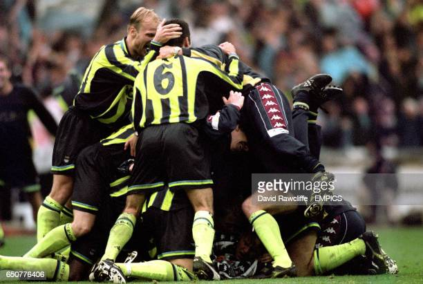 Manchester City's players bury their goalkeeper Nick Weaver after winning the Second Division PlayOff against Gillingham