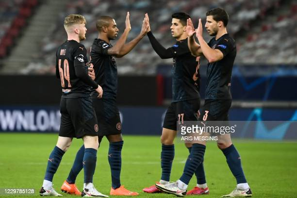 Manchester City's players celebrate their victory at the end of the UEFA Champions League group stage football match between Olympiakos and...