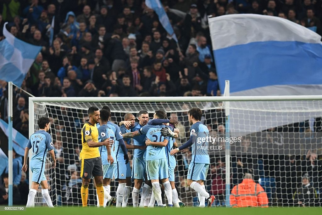Manchester City's players celebrate their victory on the pitch after the English Premier League football match between Manchester City and Arsenal at the Etihad Stadium in Manchester, north west England, on December 18, 2016. Manchester City won the game 2-1. / AFP / Paul ELLIS / RESTRICTED TO EDITORIAL USE. No use with unauthorized audio, video, data, fixture lists, club/league logos or 'live' services. Online in-match use limited to 75 images, no video emulation. No use in betting, games or single club/league/player publications. /