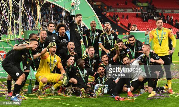 Manchester City's players celebrate with the trophy on the pitch after the English League Cup final football match between Aston Villa and Manchester...