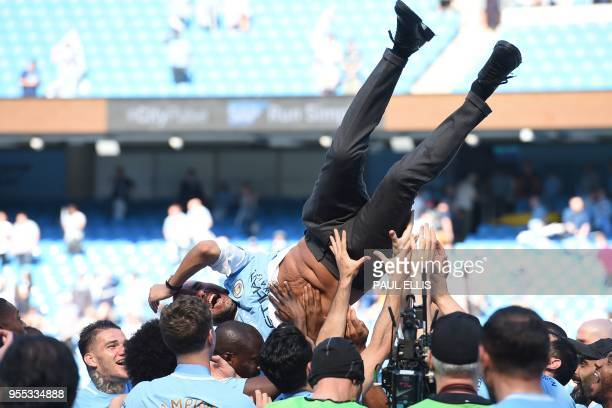 Manchester City's players lift Manchester City's Spanish manager Pep Guardiola into the air as they celebrate their title triumph on the pitch after...