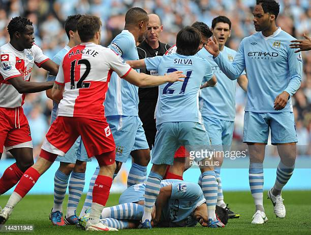 Manchester City's players surround the referee Mike Dean after Queens Park Rangers' English midfielder Joey Barton is involved in an incident with...