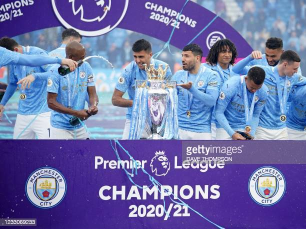 Manchester City's Portuguese defender Joao Cancelo and Manchester City's Argentinian striker Sergio Aguero stand with the Premier League trophy...