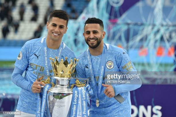 Manchester City's Portuguese defender Joao Cancelo and Manchester City's Algerian midfielder Riyad Mahrez hold the Premier League trophy during the...