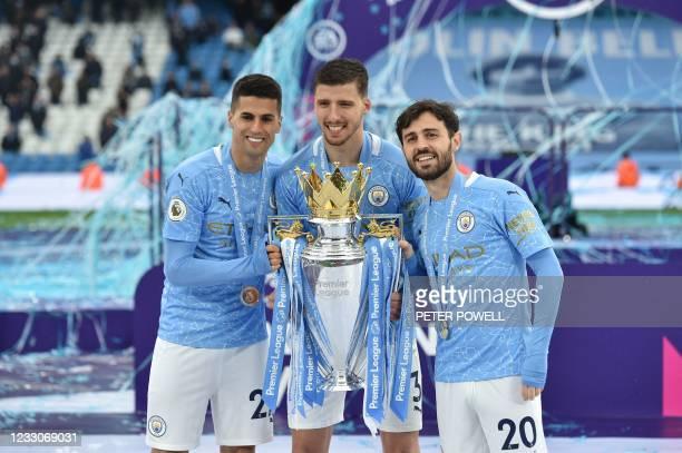 Manchester City's Portuguese defender Joao Cancelo , Manchester City's Portuguese defender Ruben Dias and Manchester City's Portuguese midfielder...