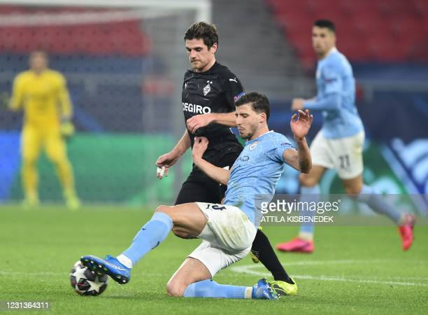 Manchester City's Portuguese defender Ruben Dias and Moenchengladbach's German midfielder Jonas Hofmann vie for the ball during the UEFA Champions...