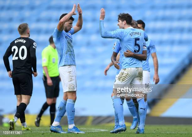 Manchester City's Portuguese defender Ruben Dias celebrates with Manchester City's English defender John Stones after the final whistle during the...