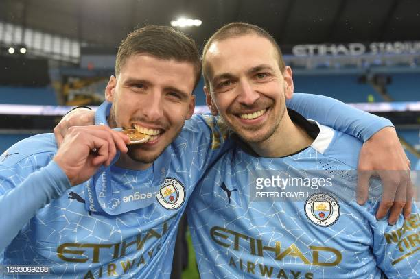 Manchester City's Portuguese defender Ruben Dias poses with his medal during the Premier League trophy award ceremony after the English Premier...