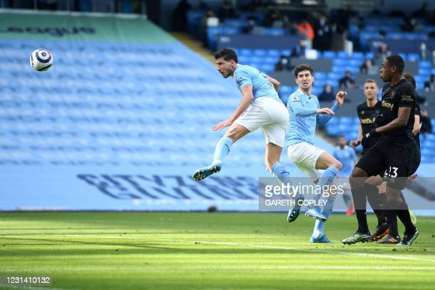 Manchester City's Portuguese defender Ruben Dias scores the opening goal during the English Premier League football match between Manchester City and...