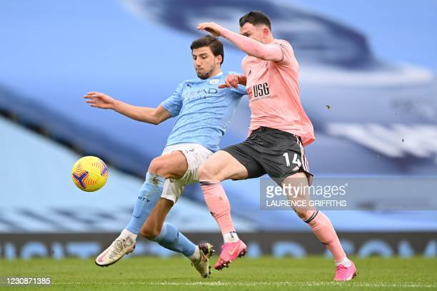Manchester City's Portuguese defender Ruben Dias tackles Sheffield United's Scottish striker Oliver Burke during the English Premier League football...