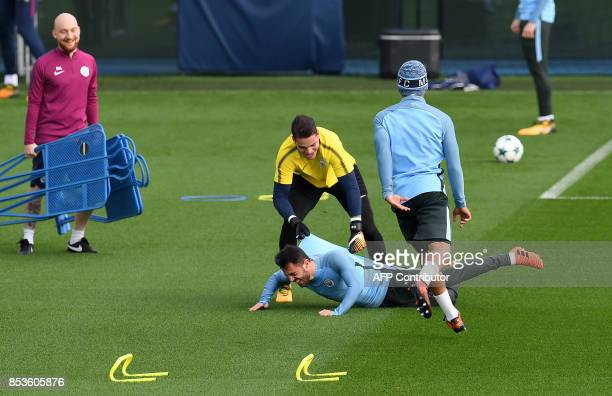 Manchester City's Portuguese midfielder Bernardo Silva and Manchester City's Brazilian goalkeeper Ederson joke during a training session at the City...