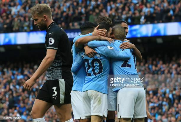 Manchester City's Portuguese midfielder Bernardo Silva celebrates with teammates after scoring their second goal during the English Premier League...