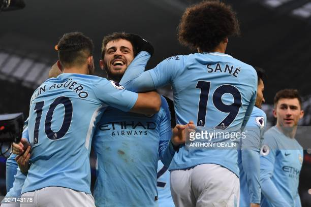 Manchester City's Portuguese midfielder Bernardo Silva celebrates with tammates scoring the opening goal during the English Premier League football...