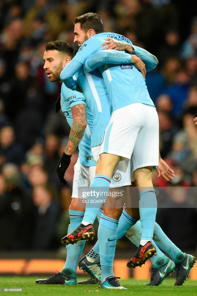 Manchester City's Portuguese midfielder Bernardo Silva is picked up by Manchester City's Brazilian defender Danilo as they celebrate their fourth goal during the English FA Cup third round football match between Manchester City and Burnley at Etihad Stadium in Manchester, north west England on January 6, 2018. / AFP PHOTO / Oli SCARFF / RESTRICTED TO EDITORIAL USE. No use with unauthorized audio, video, data, fixture lists, club/league logos or 'live' services. Online in-match use limited to 75 images, no video emulation. No use in betting, games or single club/league/player publications. /