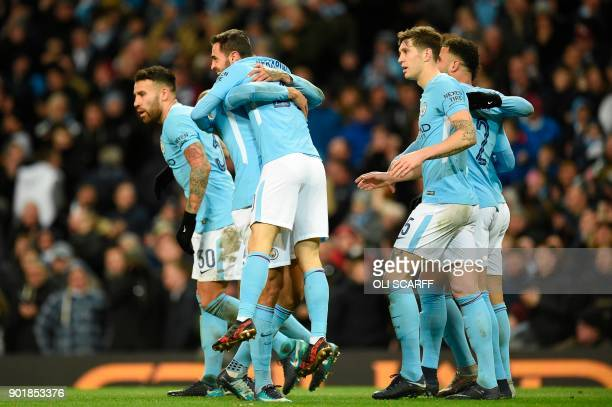 Manchester City's Portuguese midfielder Bernardo Silva is picked up by Manchester City's Brazilian defender Danilo as they celebrate their fourth...