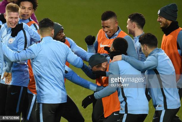Manchester City's Portuguese midfielder Bernardo Silva reacts as he is mobbed by teammates including Manchester City's Belgian midfielder Kevin De...