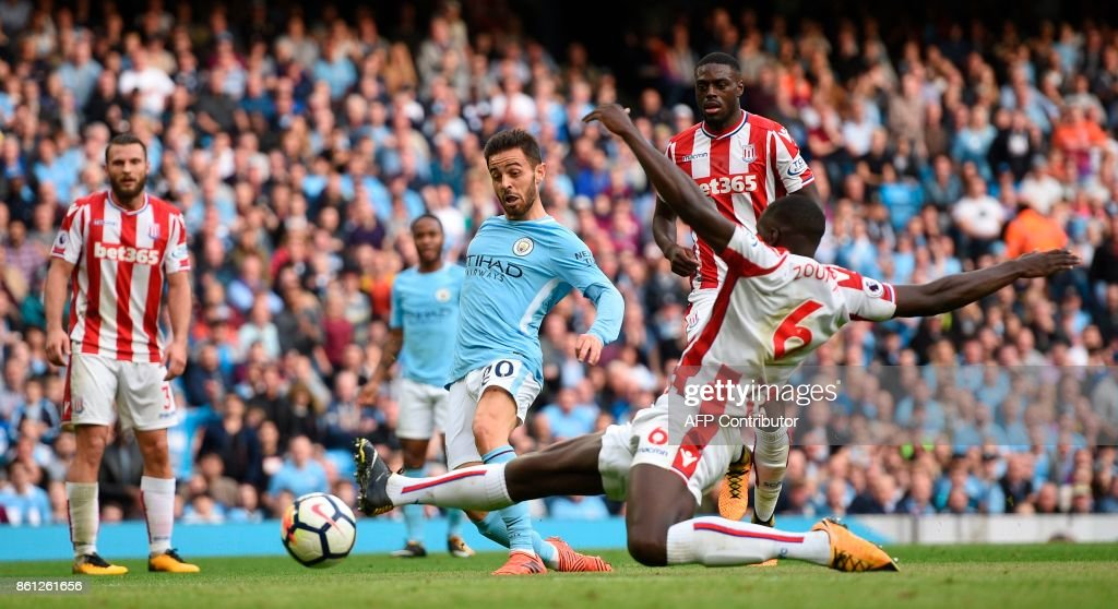 Manchester City's Portuguese midfielder Bernardo Silva (C) scores their seventh goal during the English Premier League football match between Manchester City and Stoke City at the Etihad Stadium in Manchester, north west England, on October 14, 2017. / AFP PHOTO / Oli SCARFF / RESTRICTED TO EDITORIAL USE. No use with unauthorized audio, video, data, fixture lists, club/league logos or 'live' services. Online in-match use limited to 75 images, no video emulation. No use in betting, games or single club/league/player publications. /