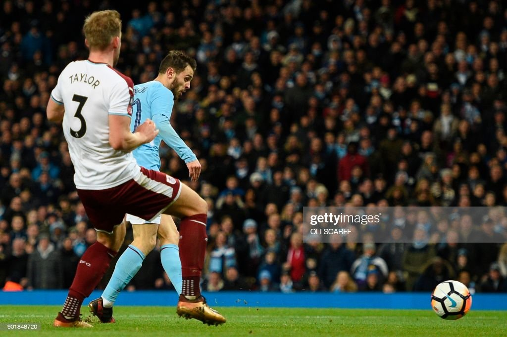 Manchester City's Portuguese midfielder Bernardo Silva (R) scores their fourth goal during the English FA Cup third round football match between Manchester City and Burnley at Etihad Stadium in Manchester, north west England on January 6, 2018. / AFP PHOTO / Oli SCARFF / RESTRICTED TO EDITORIAL USE. No use with unauthorized audio, video, data, fixture lists, club/league logos or 'live' services. Online in-match use limited to 75 images, no video emulation. No use in betting, games or single club/league/player publications. /