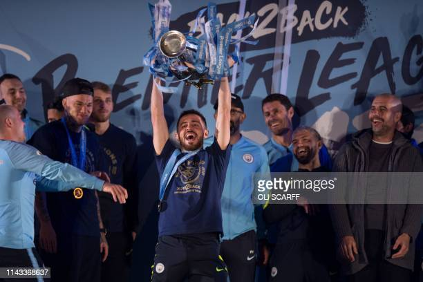 Manchester City's Portuguese midfielder Bernardo Silva shows the Premier League trophy to supporters outside the Etihad Stadium in Manchester...