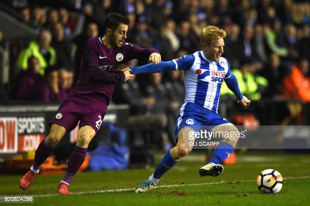 Manchester City's Portuguese midfielder Bernardo Silva vies with Wigan Athletic's English midfielder David Perkins during the English FA Cup fifth...
