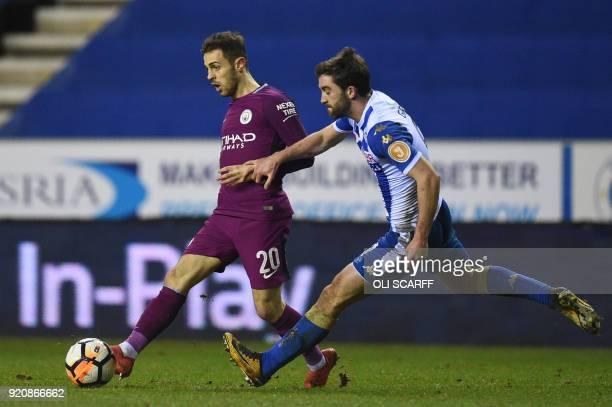 Manchester City's Portuguese midfielder Bernardo Silva vies with Wigan Athletic's Englishborn Northern Irish striker Will Grigg during the English FA...
