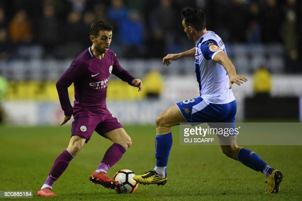 Manchester City's Portuguese midfielder Bernardo Silva vies with Wigan Athletic's English midfielder Gary Roberts during the English FA Cup fifth...