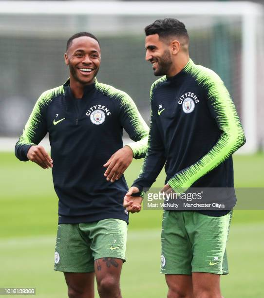 Manchester City's Raheem Sterling shares a joke with Riyad Mahrez during training at Manchester City Football Academy on August 13 2018 in Manchester...