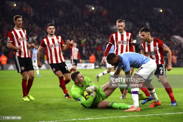 Manchester City's Raheem Sterling tries to get the ball from Sheffield United goalkeeper Dean Henderson after saving a penalty Sheffield United v...